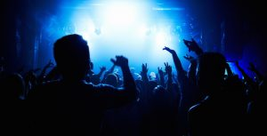 A crowd of people watching a band play on stage at a nightclub. This concert was created for the sole purpose of this photo shoot, featuring 300 models and 3 live bands. All people in this shoot are model released.http://195.154.178.81/DATA/i_collage/pi/shoots/782423.jpg
