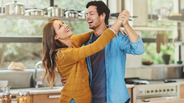 Shot of an affectionate young couple dancing in their kitchen